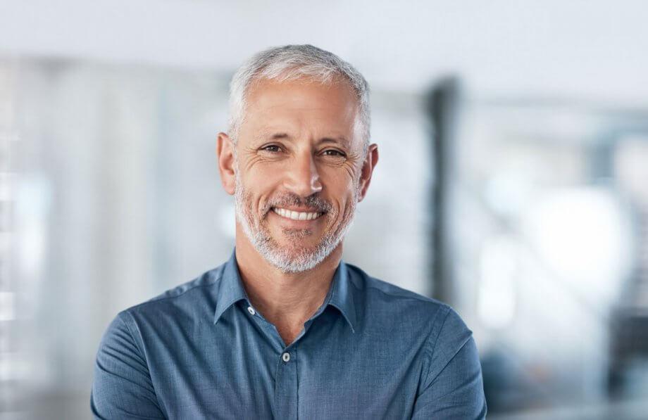 older man in blue shirt with short grey beard