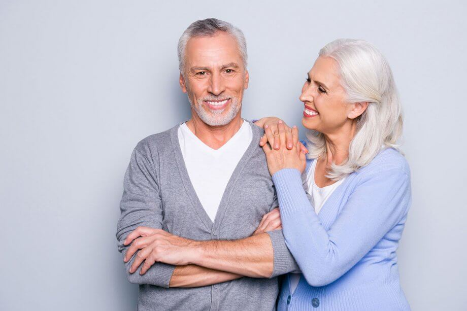senior couple against grey background, standing, smiling
