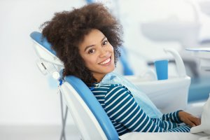 young girl in blue and white dental exam chair smiling
