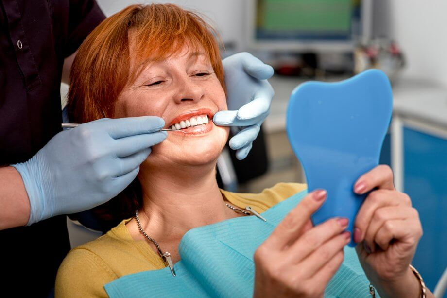 woman at dentist smiling and looking in mirror