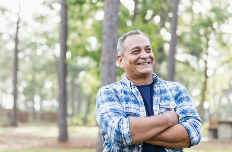 older man in blue plaid shirt standing with arms folded in the woods