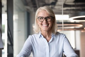 woman wearing black frame glasses standing in office, smiling