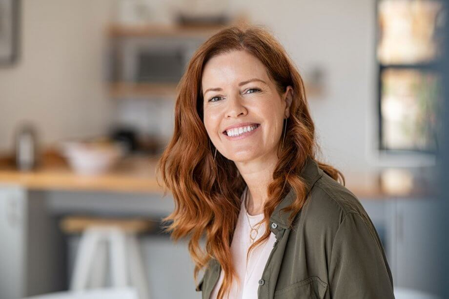 red haired woman standing in kitchen, smiling