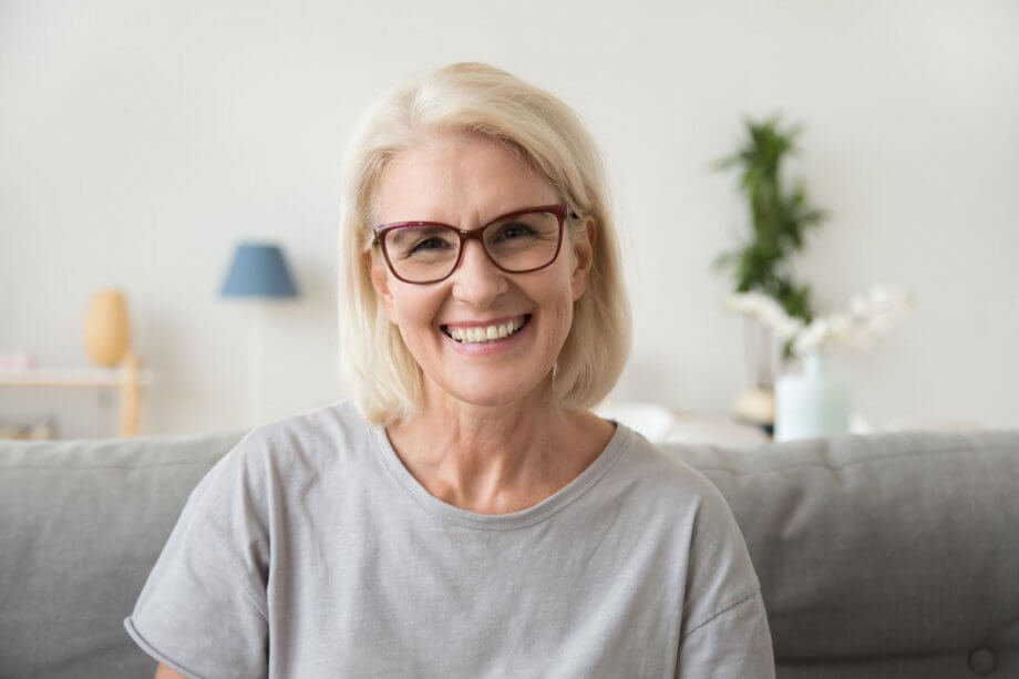 older woman in red glasses sitting on grey couch, smiling